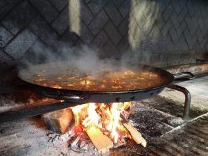 Paella cocinada a leña durante el taller concurso de paella en la Albufera de Valencia para un evento en Valencia